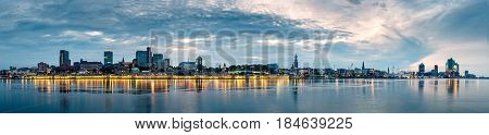 Panorama of the Hamburg Skyline in Germany at sunrise during the blue hour.