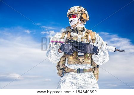 Army serviceman in winter camo somewhere in the Arctic. He wears chest rig and huge backpack suffers from the extreme cold and strong wind but endures while mission continues. Blue sky background