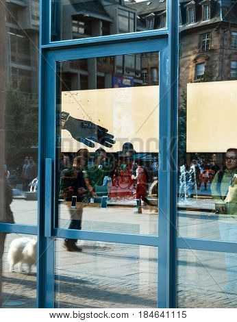 STRASBOURG FRANCE - APR 23 2017: City reflection in Apple Store window facade of the Apple Store interior with customers buying diverse computers smartphones and gadgets