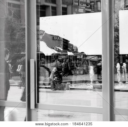 STRASBOURG FRANCE - APR 23 2017: Black and white image of general view through glass window facade of the Apple Store interior with customers buying diverse computers smartphones and gadgets