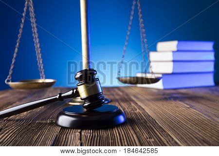 Gavel of jugde on old wooden table and blue background.  Law theme and concept.
