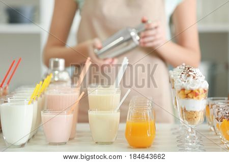Different tasty milk shakes and female bartender in bar