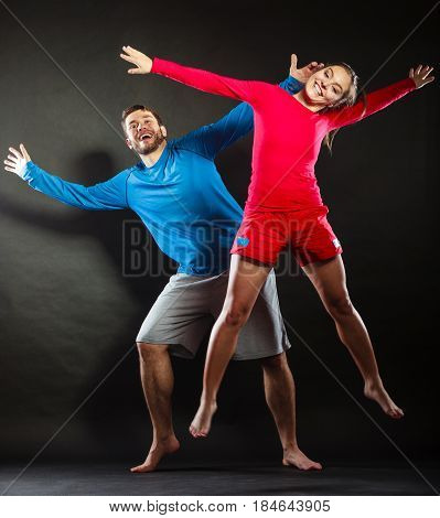 Happy joyful young couple man and woman jumping for joy in studio on black. Happiness and enjoyment. Good relationship.