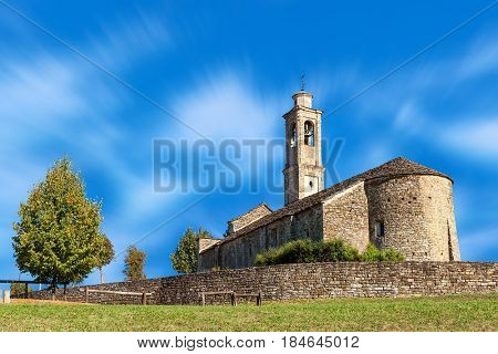 Old stone parish church under blue sky in small town of Prunetto in Piedmont, Northern Italy.