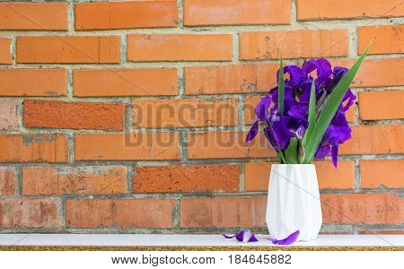 bouquet of purple iris flowers in styled vase near exposed brick wall. Empty frame mock up for presentation design. Template framing for modern art.