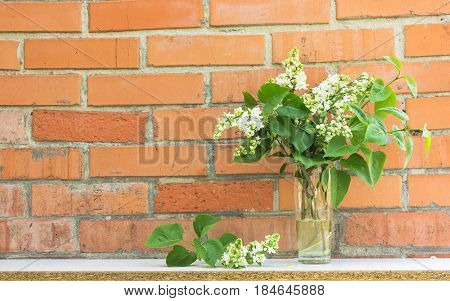 bouquet of lilac flowers in styled vase with books near exposed brick wall. Empty frame mock up for presentation design. Template framing for modern art.