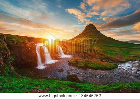 Colorful sunrise on Kirkjufellsfoss waterfall. Amazing morning scene near Kirkjufell volkano, Iceland, Europe.
