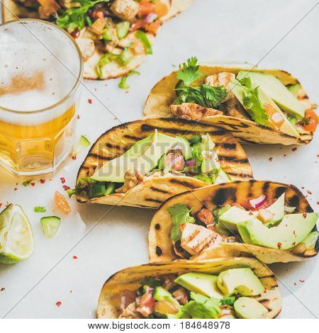 Healthy corn tortillas with grilled chicken, avocado, fresh salsa, limes, beer in glass over light grey marble background, selective focus, square crop. Healthy food, gluten-free, weight loss concept