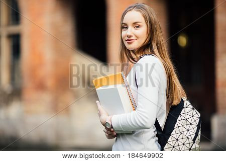 Student With Backpack And Books Outdoors Near University