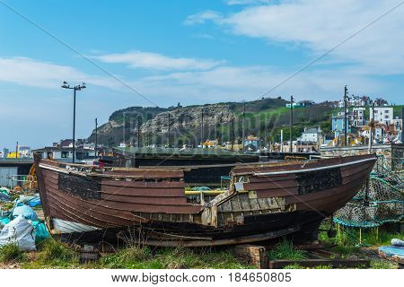 Old Wooden Destroyed Boat In A Fishing Port, On The Shore, Against The Backdrop Of A Coastal Town