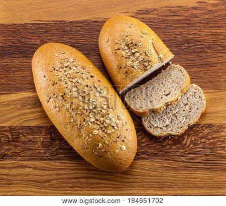 Loaf of wholegrain bread and slices on wooden background