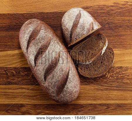 Loaf of homemade bread and slices on wooden background view from above
