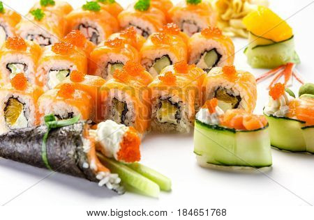 Sushi rolls with salmon temaki roll and salad rolls over white background