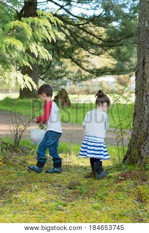 Easter egg hunt with young child hunting the eggs outdoors on a family property in Oregon.