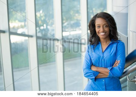 Closeup portrait young professional beautiful confident woman in blue shirt friendly personality smiling standing in front ot glass window isolated indoors office background. Positive emotions
