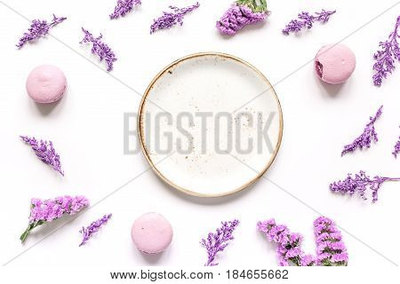lady morning with macaroons and mauve flowers on white desk background top view mockup
