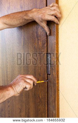 Front door installation. Worker fastens door trims with screwdriver
