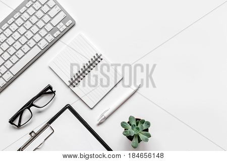 office flat lay table with keyboard, glasses, notebook on white background top view mockup