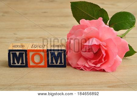 Mom spelled with colorful alphabet blocks and a pink rose