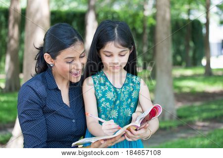 Closeup portrait young family enjoying coloring book drawing isolated outdoors outside background