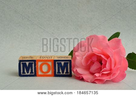 Mom spelled with colorful alphabet blocks and a pink rose isolated on a white background