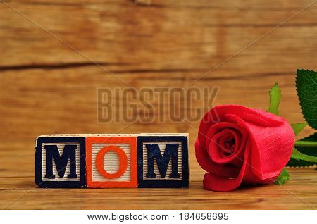 Mom spelled with colorful alphabet blocks and a red rose