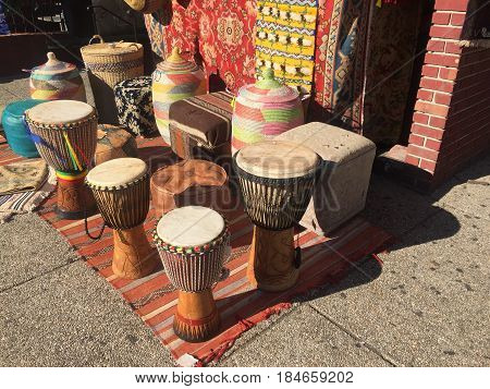 Drums, rugs and ottomans on a sidewalk