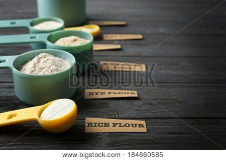 Measuring scoops with different types of flour on wooden background