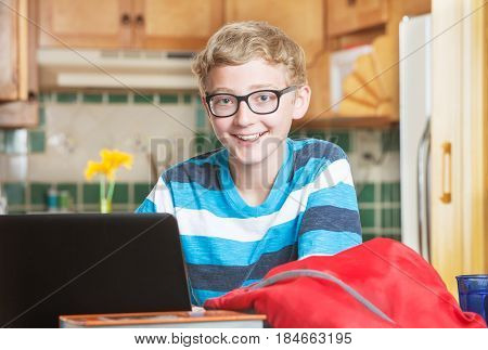 Cute single smiling boy in eyeglasses and striped shirt using laptop