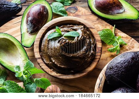 Vegan food. Raw avocado chocolate mousse pudding with mint in olive wooden bowl. Organic healthy dessert