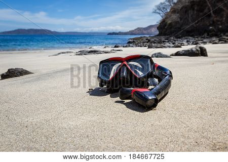 wide angle close up of a snorkeling mask and tube on a relaxing beach with blue water in the background.
