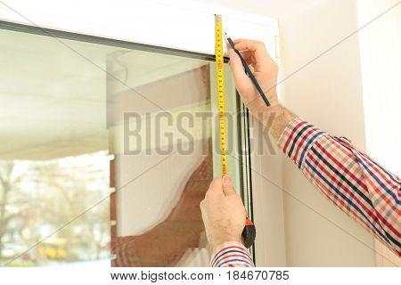 Male hands marking off window frame