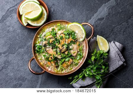 Latin American ceviche o mariscal - raw seafood cold soup wish mussels, clams, prawns, lime, onion in copper bowl on slate background. Seafood shellfish ceviche. Traditional dish of Peru or Chile