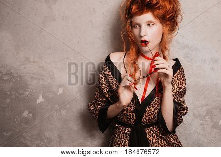 A woman with glasses and red hair in leopard print gown with glasses in hand. Red-haired in glasses girl with pale skin and blue eyes with a bright unusual appearance with a red ribbon around her neck. French courtesan with glasses. Concept with glasses