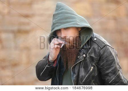 Bearded man smoking weed outdoors