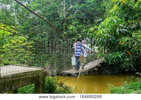Beaufort,Sabah-June 25,2016:The villagers are walking on a suspension bridge on an early morning in Lingkungan,Beaufort,Sabah.The suspension bridge made form steel cables and planks was equally wide.