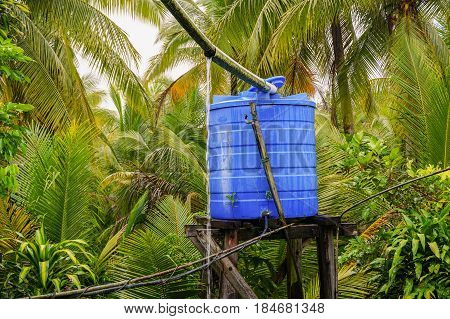 Blue water tank outdoor during raining day with water leaking out from tank & background of tropical jungle