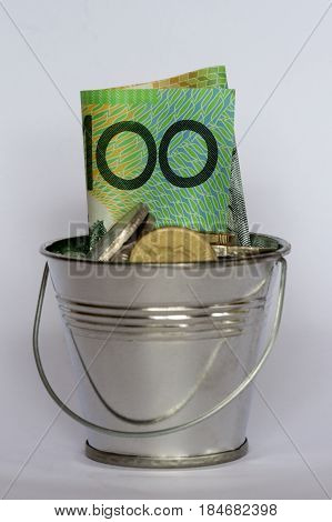 A bucket containing an Australian hundred dollar note and coins.