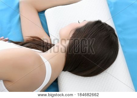 Young woman lying on bed with orthopedic pillow at home. Healthy posture concept