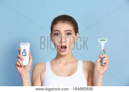 Beautiful young woman with razor and epilator on color background