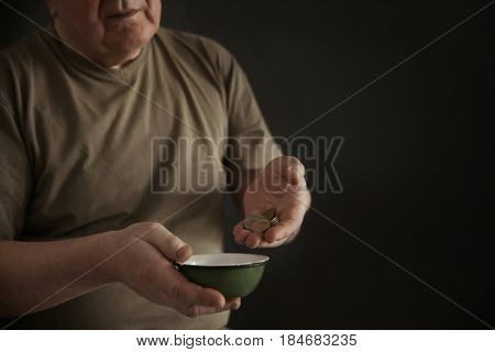 Senior man with bowl and coins on dark background, closeup. Poverty concept