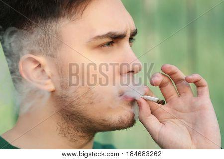 Handsome young man smoking weed outdoors, closeup