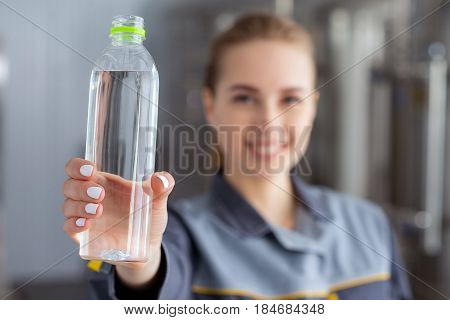 Specialist with bottle of pure water at a water factory