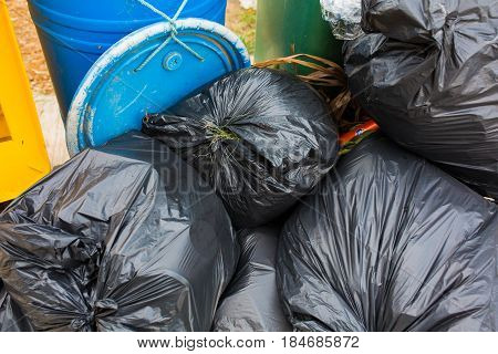 Piles of garbage in plastic bin bags (trash, waste) in City.