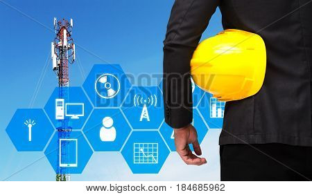 businessman with yellow safety helmet with technology device icon and hexagon shaped pattern background with telecommunication tower with blue sky technology business industrial concept