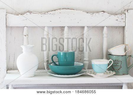 the dinnerware on old white wooden shelf