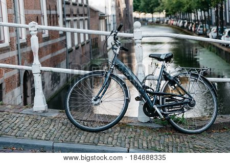 Delft Netherlands - August 3 2016: Bicycle parked on the bridge in a picturesque street in the dutch city of Delft