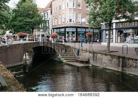 Delft Netherlands - August 3 2016: Cityscape of Delft with picturesque buildings bridge canals and cobble pavement