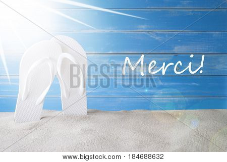 French Text Merci Means Thank You. Sunny Summer Greeting Card With Sand And Flip Flops. Blue Vintage And Shabby Chic Wooden Background.