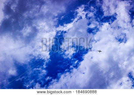 Plane against partly cloudy and btrilliant blue sky.